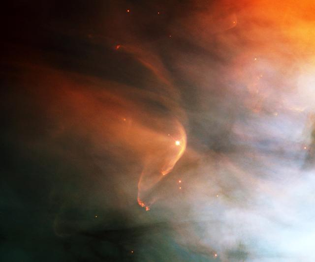 The nearby intense star-forming region known as the Great Nebula in the Orion constellation reveals a bow shock around a very young star as seen by NASA's Hubble Space Telescope (HST). Named for the crescent-shaped wave made by a ship as it moves through the water, a bow shock can be created in space where two streams of gas collide. LL Ori emits a vigorous solar wind, a stream of charged particles moving rapidly outward from the star. Our own sun has a less energetic version of this wind. The material in the fast wind from LL Ori collides with slow moving gas evaporating away form the center of the Orion Nebula, which is located in the lower right of this image, producing the crescent shaped bow shock seen in the image. Astronomers have identified numerous shock fronts in this complex star-forming region and are using this data to understand the many complex phenomena associated with the birth of stars. A close visitor in our Milky Way Galaxy, the nebula is only 1,500 light years away from Earth. The filters used in this color composite represent oxygen, nitrogen, and hydrogen emissions.
