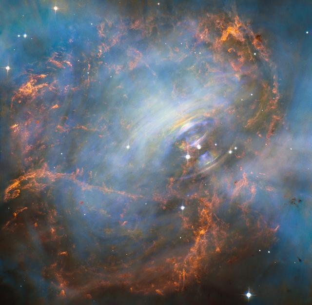 Peering deep into the core of the Crab Nebula, this close-up image reveals the beating heart of one of the most historic and intensively studied remnants of a supernova, an exploding star. The inner region sends out clock-like pulses of radiation and tsunamis of charged particles embedded in magnetic fields.  The neutron star at the very center of the Crab Nebula has about the same mass as the sun but compressed into an incredibly dense sphere that is only a few miles across. Spinning 30 times a second, the neutron star shoots out detectable beams of energy that make it look like it's pulsating.  The NASA Hubble Space Telescope snapshot is centered on the region around the neutron star (the rightmost of the two bright stars near the center of this image) and the expanding, tattered, filamentary debris surrounding it. Hubble's sharp view captures the intricate details of glowing gas, shown in red, that forms a swirling medley of cavities and filaments. Inside this shell is a ghostly blue glow that is radiation given off by electrons spiraling at nearly the speed of light in the powerful magnetic field around the crushed stellar core.  The neutron star is a showcase for extreme physical processes and unimaginable cosmic violence. Bright wisps are moving outward from the neutron star at half the speed of light to form an expanding ring. It is thought that these wisps originate from a shock wave that turns the high-speed wind from the neutron star into extremely energetic particles.  When this &quot;heartbeat&quot; radiation signature was first discovered in 1968, astronomers realized they had discovered a new type of astronomical object. Now astronomers know it's the archetype of a class of supernova remnants called pulsars - or rapidly spinning neutron stars. These interstellar &quot;lighthouse beacons&quot; are invaluable for doing observational experiments on a variety of astronomical phenomena, including measuring gravity waves.  Observations of the Crab supernova 