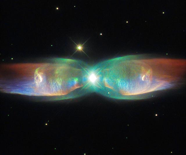 """The shimmering colors visible in this NASA/ESA Hubble Space Telescope image show off the remarkable complexity of the Twin Jet Nebula. The new image highlights the nebula's shells and its knots of expanding gas in striking detail. Two iridescent lobes of material stretch outwards from a central star system. Within these lobes two huge jets of gas are streaming from the star system at speeds in excess of one million kilometers (621,400 miles) per hour.  Read more: <a href=""""http://go.nasa.gov/1hGASfl"""" rel=""""nofollow"""">go.nasa.gov/1hGASfl</a>  Credit: ESA/Hubble &amp; NASA, Acknowledgement: Judy Schmidt  <b><a href=""""http://www.nasa.gov/audience/formedia/features/MP_Photo_Guidelines.html"""" rel=""""nofollow"""">NASA image use policy.</a></b>  <b><a href=""""http://www.nasa.gov/centers/goddard/home/index.html"""" rel=""""nofollow"""">NASA Goddard Space Flight Center</a></b> enables NASA's mission through four scientific endeavors: Earth Science, Heliophysics, Solar System Exploration, and Astrophysics. Goddard plays a leading role in NASA's accomplishments by contributing compelling scientific knowledge to advance the Agency's mission.  <b>Follow us on <a href=""""http://twitter.com/NASAGoddardPix"""" rel=""""nofollow"""">Twitter</a></b>  <b>Like us on <a href=""""http://www.facebook.com/pages/Greenbelt-MD/NASA-Goddard/395013845897?ref=tsd"""" rel=""""nofollow"""">Facebook</a></b>  <b>Find us on <a href=""""http://instagrid.me/nasagoddard/?vm=grid"""" rel=""""nofollow"""">Instagram</a></b>"""