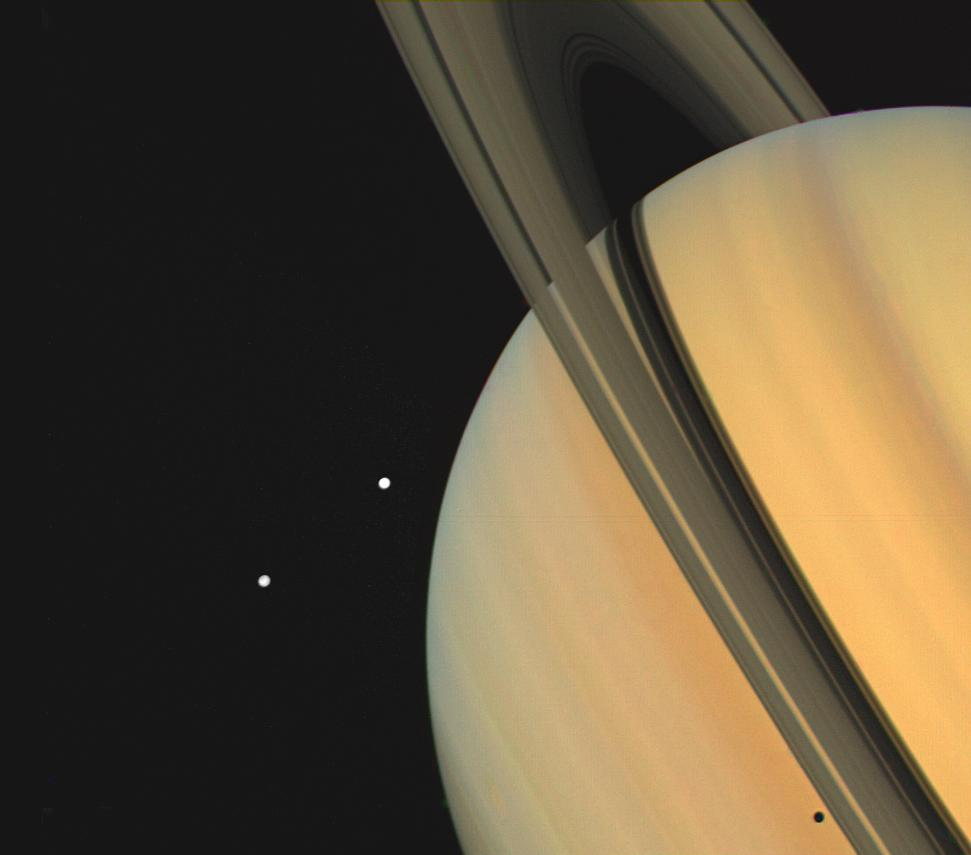 Saturn and two of its moons, Tethys above and Dione, were photographed by Voyager 1 on November 3, 1980, from 13 million kilometers (8 million miles).