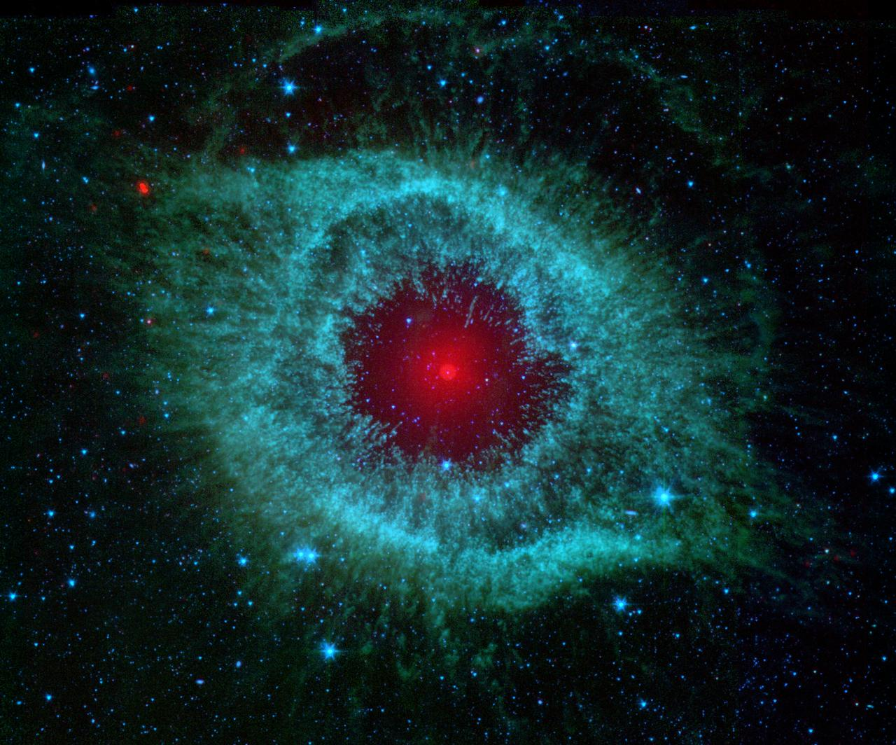 This infrared image from NASA Spitzer Space Telescope shows the Helix nebula, a cosmic starlet often photographed by amateur astronomers for its vivid colors and eerie resemblance to a giant eye.