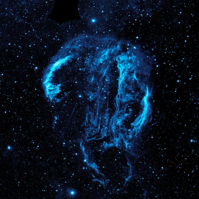 Wispy tendrils of hot dust and gas glow brightly in this ultraviolet image of the Cygnus Loop nebula, taken by NASA Galaxy Evolution Explorer. The nebula lies about 1,500 light-years away.