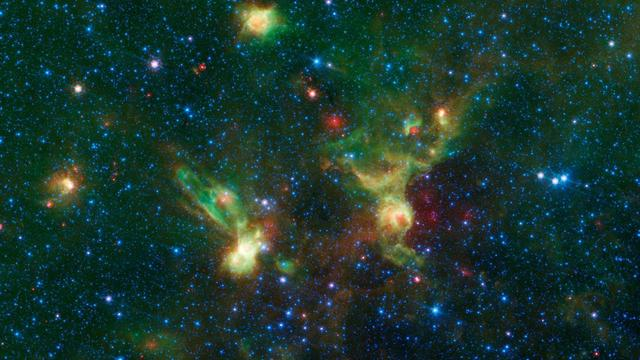"""Just in time for the 50th anniversary of the TV series """"Star Trek,"""" which first aired September 8th,1966, this infrared image from NASA's Spitzer Space Telescope may remind fans of the historic show. Just as one might see the shapes of animals or other objects in clouds -- a phenomenon called pareidolia -- iconic starships from the series may seem to emerge in these nebulae./  With a little scrutiny (see Figure 1), you may see hints of the saucer and hull of the original USS Enterprise, captained by James T. Kirk, as if it were emerging from a dark nebula. To the left, its """"Next Generation"""" successor, Jean-Luc Picard's Enterprise-D, flies off in the opposite direction.  Astronomically speaking, the region pictured here falls within the disk of our Milky Way galaxy, and displays two regions of star formation that are hidden behind a haze of dust when viewed in visible light. Spitzer's ability to peer deeper into dust clouds has revealed a myriad of stellar birthplaces like these, which are officially known only by their catalog numbers, IRAS 19340+2016 and IRAS19343+2026.  Trekkies, however, may prefer using the more familiar designations NCC-1701 and NCC-1701-D.  This image was assembled using data from Spitzer's biggest surveys of the Milky Way, called GLIMPSE and MIPSGAL. Light with a wavelength of 3.5 microns is shown in blue, 8.0 microns is green, and 24 microns in red. The green colors highlight organic molecules in the dust clouds, illuminated by starlight. Red colors are related to thermal radiation emitted from the very hottest areas of dust.  http://photojournal.jpl.nasa.gov/catalog/PIA20917"""