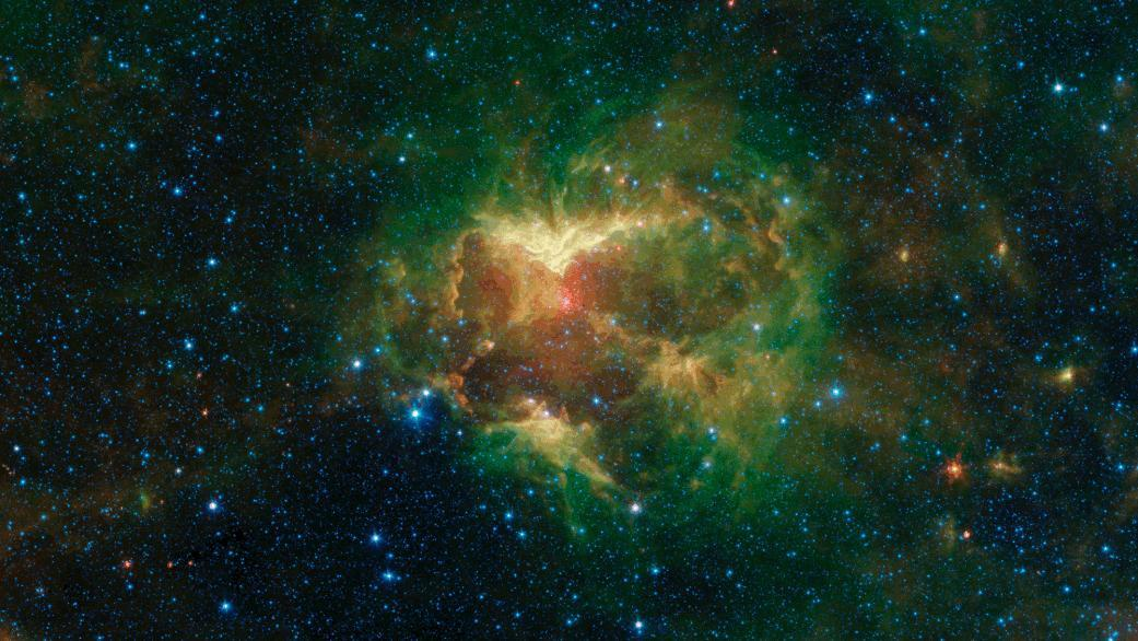 """This carved-out cloud of gas and dust has been nicknamed the """"Jack-o'-lantern Nebula"""" because it looks like a cosmic hollowed-out pumpkin. Powerful outflows of radiation and particles from a massive star — known as an O-type star and about 15 to 20 times heavier than the Sun — has likely swept the surrounding dust and gas outward, creating deep gouges in the cloud. The image shows infrared light (which is invisible to the human eye) captured by NASA's Spitzer Space Telescope.  https://photojournal.jpl.nasa.gov/catalog/PIA23403"""