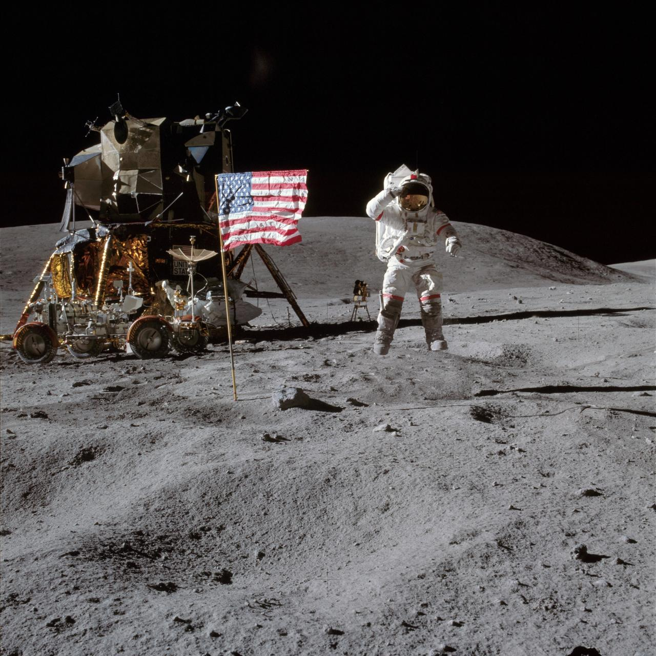 "AS16-113-18339 (21 April 1972) --- Astronaut John W. Young, commander of the Apollo 16 lunar landing mission, leaps from the lunar surface as he salutes the United States flag at the Descartes landing site during the first Apollo 16 extravehicular activity (EVA).  Astronaut Charles M. Duke Jr., lunar module pilot, took this picture. The Lunar Module (LM) ""Orion"" is on the left. The Lunar Roving Vehicle (LRV) is parked beside the LM. The object behind Young (in the shade of the LM) is the Far Ultraviolet Camera/Spectrograph (FUC/S). Stone Mountain dominates the background in this lunar scene. While astronauts Young and Duke descended in the LM to explore the Descartes highlands landing site on the moon, astronaut Thomas K. Mattingly II, command module pilot, remained with the Command and Service Modules (CSM) ""Casper"" in lunar orbit."