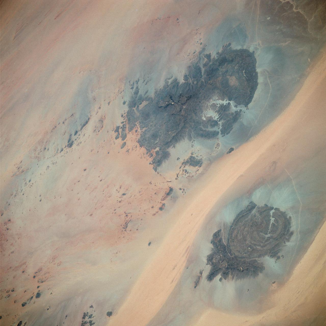 AST-02-130 (20 July 1975) --- An oblique view of a portion of Libya and the Arab Republic of Egypt, as photographed from the Apollo spacecraft in Earth orbit during the joint U.S.-USSR Apollo-Soyuz Test Project mission. The geological features are the Jebel Uweinat and Jebel Arkenu basaltic mountains in the Libyan sand sea. This picture was taken with a 70mm Hasselblad camera using medium-speed Ektachrome QX-807 type film.  The spacecraft was at an altitude of 219 kilometers (136 statute miles).