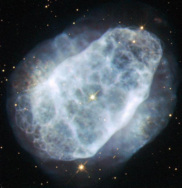 This NASA/ESA Hubble Space Telescope image shows a planetary nebula named NGC 6153, located about 4000 light-years away in the southern constellation of Scorpius (The Scorpion). The faint blue haze across the frame shows what remains of a star like the Sun after it has depleted most of its fuel. When this happens, the outer layers of the star are ejected, and get excited and ionised by the energetic ultraviolet light emitted by the bright hot core of the star, forming the nebula. NGC 6153 is a planetary nebula that is elliptical in shape, with an extremely rich network of loops and filaments, shown clearly in this Hubble image. However, this is not what makes this planetary nebula so interesting for astronomers. Measurements show that NGC 6153 contains large amounts of neon, argon, oxygen, carbon and chlorine — up to three times more than can be found in the Solar System. The nebula contains a whopping five times more nitrogen than the Sun! Although it may be that the star developed higher levels of these elements as it grew and evolved, it is more likely that the star originally formed from a cloud of material that already contained lots more of these elements. A version of this image was entered into the Hubble's Hidden Treasures image processing competition by contestant Matej Novak. Links  Matej Novak's image on Flickr