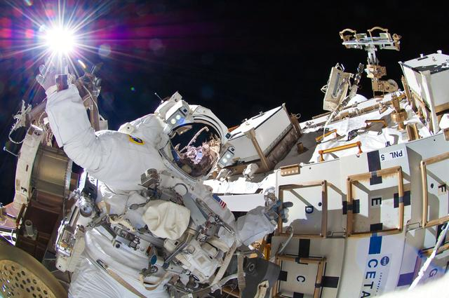 ISS032-E-025274 (5 Sept. 2012) --- NASA astronaut Sunita Williams, Expedition 32 flight engineer, appears to touch the bright sun during the mission?s third session of extravehicular activity (EVA). During the six-hour, 28-minute spacewalk, Williams and Japan Aerospace Exploration Agency astronaut Aki Hoshide (visible in the reflections of Williams? helmet visor), flight engineer, completed the installation of a Main Bus Switching Unit (MBSU) that was hampered last week by a possible misalignment and damaged threads where a bolt must be placed. They also installed a camera on the International Space Station?s robotic arm, Canadarm2.