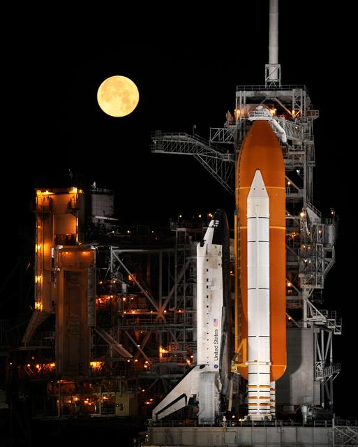 A nearly full Moon sets as the space shuttle Discovery sits atop Launch pad 39A at the Kennedy Space Center in Cape Canaveral, Florida, Wednesday, March 11, 2009.  Photo Credit: (NASA/Bill Ingalls)